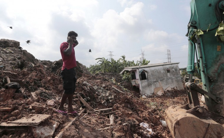 In this Saturday, April 15, 2017 photo, a Sri Lankan man speaks on his mobile phone at the site of buried houses in a collapse of a garbage dump in Meetotamulla, on the outskirts of Colombo, Sri Lanka. A part of the garbage dump that had been used in recent years to dump the waste from capital Colombo collapsed destroying houses, according to local media reports. (AP Photo/Eranga Jayawardena, File)