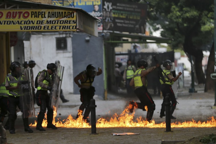 Bolivarian National Police run through flames during clashes with anti-government protesters in Caracas, Venezuela, Thursday, April 20, 2017. Tens of thousands of protesters asking for the resignation of President Nicolas Maduro flooded the streets again Thursday, one day after three people were killed and hundreds arrested in the biggest anti-government demonstrations in years. (AP Photo/Fernando Llano)