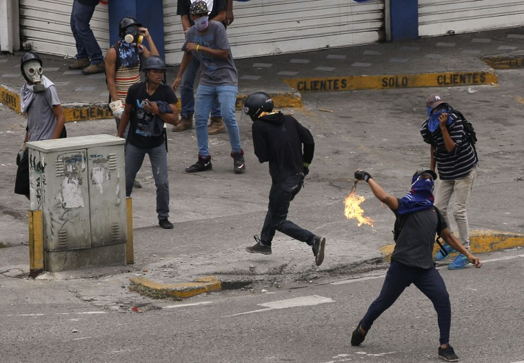 An anti-government demonstrator throws a molotov bomb during clashes in Caracas, Venezuela, Thursday, April 20, 2017. Tens of thousands of protesters flooded the streets again Thursday, one day after three people were killed and hundreds arrested in the biggest anti-government demonstrations in years. (AP Photo/Ariana Cubillos)