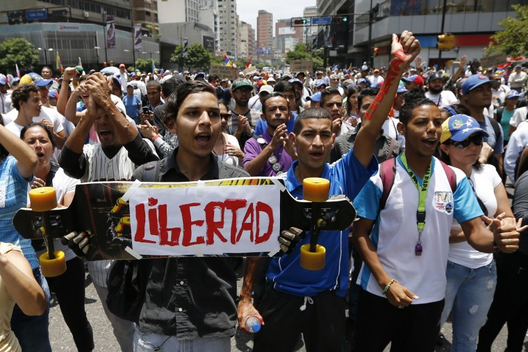 Opponents of President Nicolas Maduro march in Caracas, Venezuela, Thursday, April 20, 2017. Tens of thousands of protesters flooded the streets again Thursday, one day after three people were killed and hundreds arrested in the biggest anti-government demonstrations in years. (AP Photo/Ariana Cubillos)