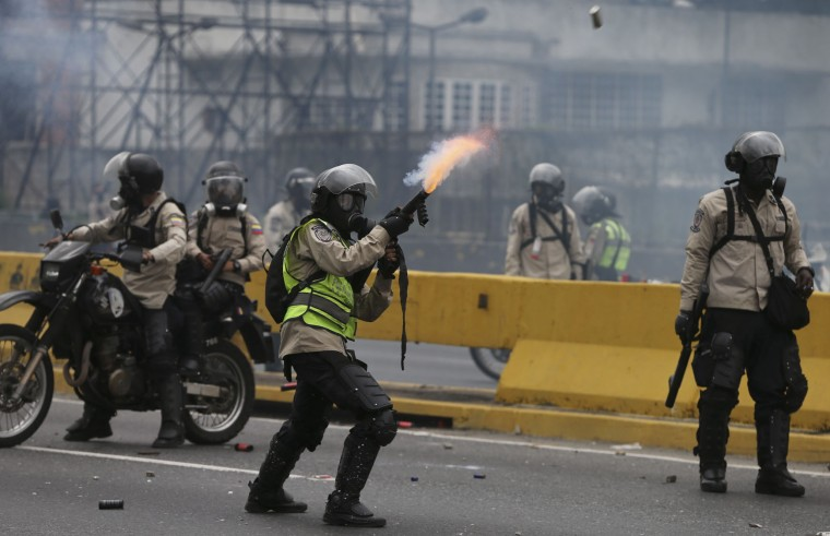 A police officer fires tear gas against anti-government protesters in Caracas, Venezuela, Thursday, April 20, 2017. Venezuela's opposition looks to keep up pressure on President Nicolas Maduro, taking to the streets again one day after three people were killed and hundreds arrested in the biggest anti-government demonstrations in years. (AP Photo/Fernando Llano)