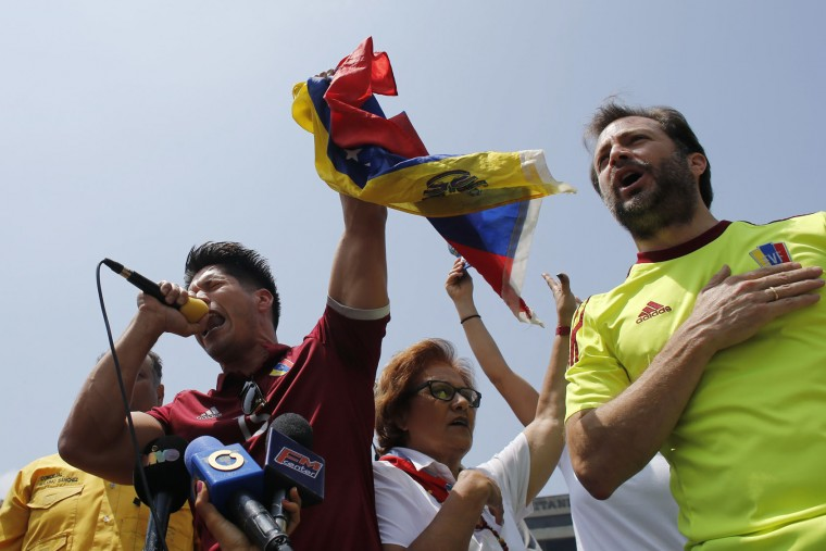 Venezuelan singer Jesus Alberto Miranda, known as Chino, left, and the Ramon Muchacho, mayor of Chacao, sing the national anthem during anti-government protests in Caracas, Venezuela, Thursday, April 20, 2017. Venezuela's opposition is calling for another day of protests against President Maduro after mass demonstrations Wednesday resulted in two deaths. (AP Photo/Ariana Cubillos)