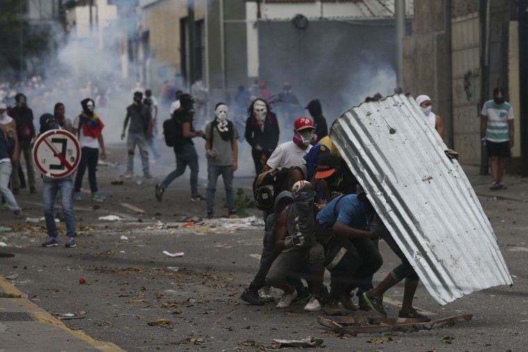 """Demonstrators take cover with a piece of corrugated tin roofing during anti-government protests in Caracas, Venezuela, Wednesday, April 19, 2017. Tens of thousands of opponents of President Nicolas Maduro flooded the streets of Caracas in what's been dubbed the """"mother of all marches"""" against the embattled president. (AP Photo/Fernando Llano)"""