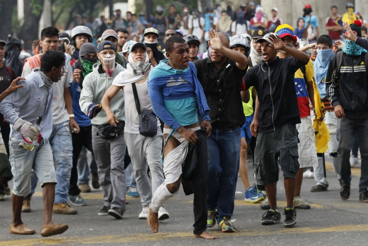 "Demonstrators escort a man that was beaten, accused of been a thief, during anti-government protests in Caracas, Venezuela, Wednesday, April 19, 2017. Tens of thousands of opponents of President Nicolas Maduro flooded the streets of Caracas in what's been dubbed the ""mother of all marches"" against the embattled socialist president. (AP Photo/Ariana Cubillos)"