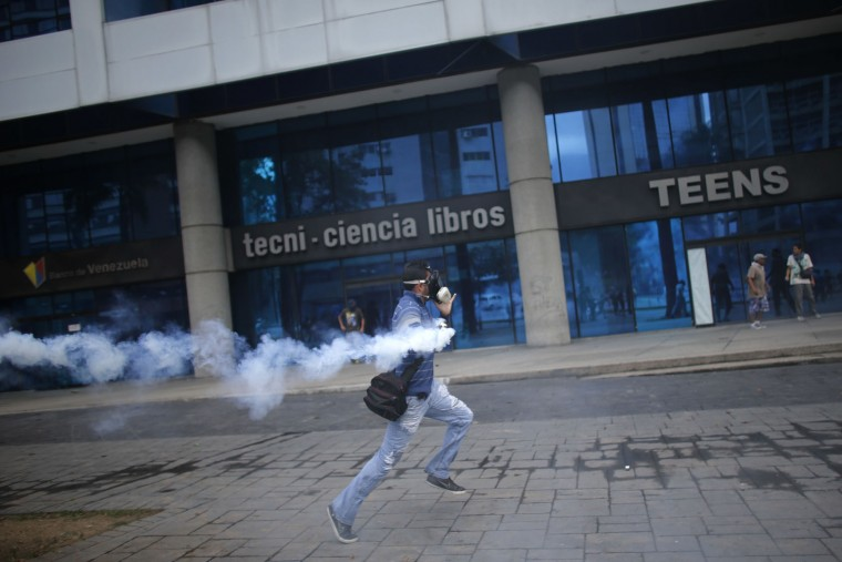 An anti-government protester runs with a canister of tear gas fired by police in Caracas, Venezuela, Thursday, April 20, 2017. Tens of thousands of protesters asking for the resignation of President Nicolas Maduro flooded the streets again Thursday, one day after three people were killed and hundreds arrested in the biggest anti-government demonstrations in years. (AP Photo/Ariana Cubillos)