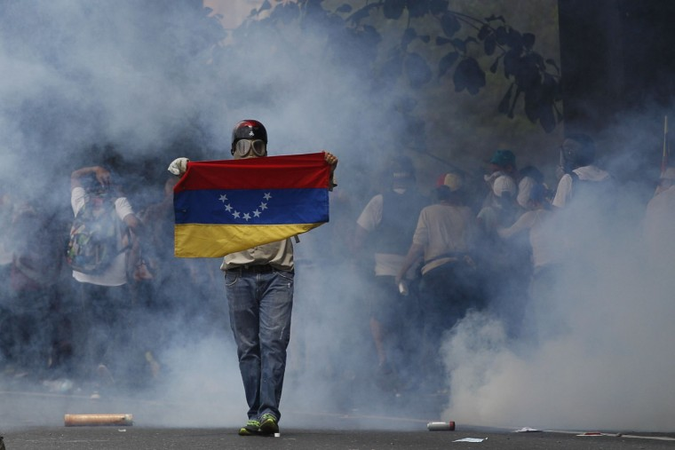 An anti-government protester holds a Venezuelan flag during clashes against security forces in Caracas, Venezuela, Wednesday, April 19, 2017. Opponents of President Nicolas Maduro called on Venezuelans to take to the streets in marched against the embattled socialist leader. (AP Photo/Ariana Cubillos)