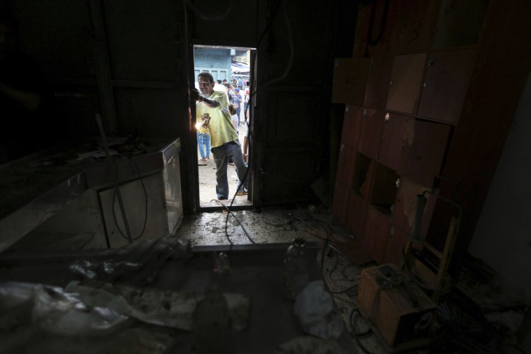 An employee fixes the main door of a supermarket looted the night before in the El Valle neighborhood in Caracas, Venezuela, Friday, April 21, 2017. At least 12 people were killed overnight following looting and violence in Venezuela's capital amid a spiraling political crisis, authorities said Friday. Most of the deaths took place in El Valle, a working class neighborhood near Caracas' biggest military base where opposition leaders say a group of people were hit with an electrical current while trying to loot a bakery protected by an electric fence. (AP Photo/Fernando Llano)
