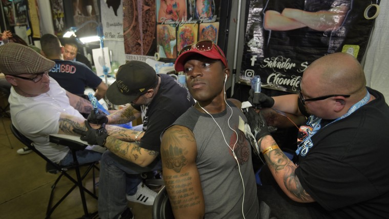 "From left, Jake Hufnagle, 34, from Baltimore gets a tattoo of a woman's head from artist John ""Johnny Fitswell"" Sanchez from San Antonio, TX,  while Quince Lanford from Ft. Meade, MD gets a lion tattoo from artist Salvador Sevilla from Palm Springs,  CA.  (Algerina Perna/Baltimore Sun)"