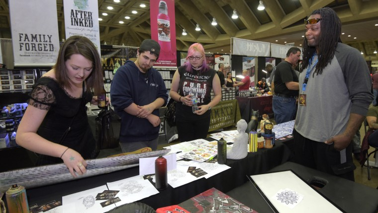From left Alycia Davis, 26 from Arbutus, Joshua Hamilton, 21 and Robin Mims, 28, both from Easton, look at work by Alex McFar, right, and the Art of War Tattoo Collective.(Algerina Perna/Baltimore Sun)