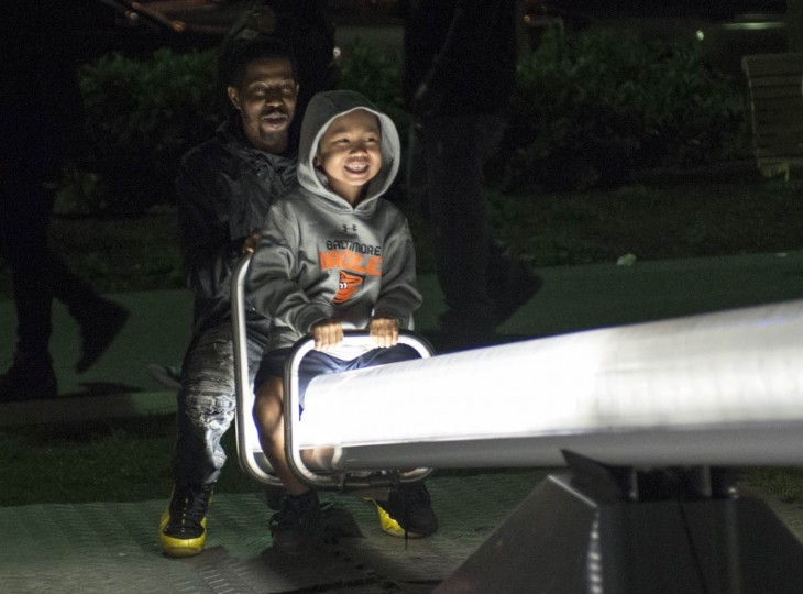 Jayden Wright, 6, and his father, James Christian of West Baltimore ride illuminated seesaws that are part of the installation, Impulse, at Light City Baltimore on Wednesday, April 5, 2017. (Emma Harris, Baltimore Sun)