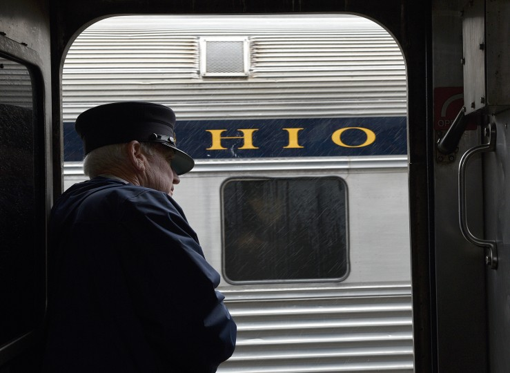 Duncan Keir, a retired federal judge who volunteers as a conductor, looks out of a train door as it returns to the station on a passenger ride at the B&O Railroad Museum. (Barbara Haddock Taylor/Baltimore Sun)