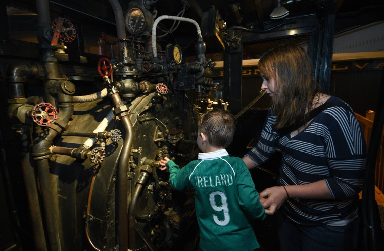Alex Granados, 3 1/2, and his mother Megan Granados of Rockford, IL, look in the engine room of the Clinchfield #1 train in the roundhouse at the B&O Railroad Museum. (Barbara Haddock Taylor/Baltimore Sun)