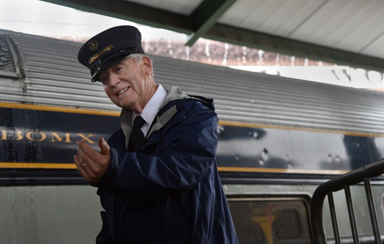 Duncan Keir, a retired federal judge who volunteers as a conductor, beckons passengers onto a train for their ride at the B&O Railroad Museum. (Barbara Haddock Taylor/Baltimore Sun)