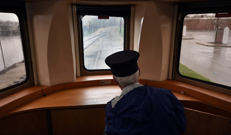 Duncan Keir, a retired federal judge who volunteers as a conductor, looks down the tracks on a passenger train ride at the B&O Railroad Museum. (Barbara Haddock Taylor/Baltimore Sun)