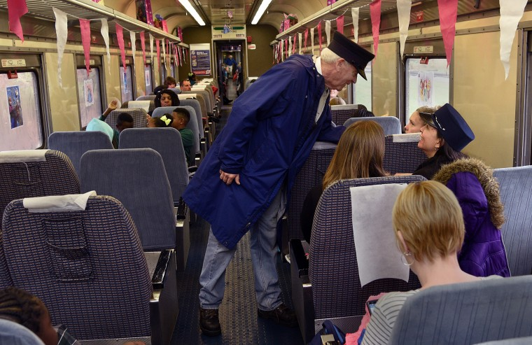 Duncan Keir, a retired federal judge who volunteers as a conductor, chats with passengers on their train ride at the B&O Railroad Museum. (Barbara Haddock Taylor/Baltimore Sun)