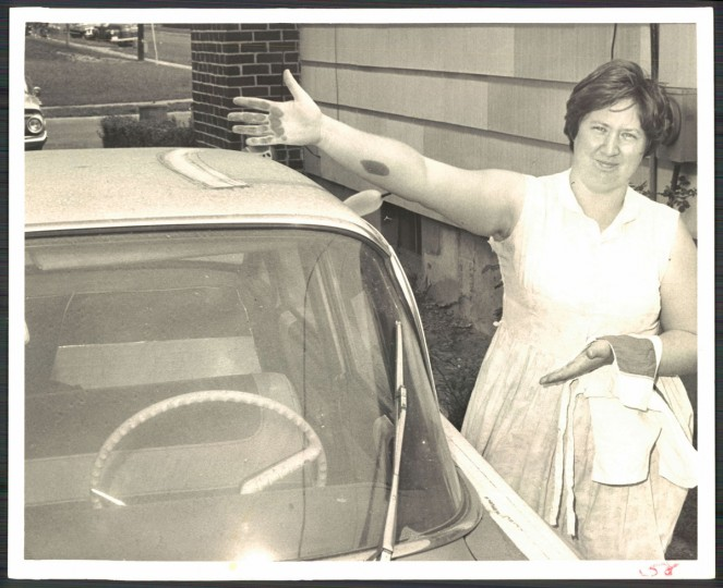 A woman wipes soot from the roof of her car in photo dated July 8, 1967. (Baltimore Sun archives)