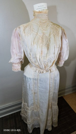 Two-piece wedding gown; beige silk decorated with a small pattern of lace; floor-length, has a single clasp at the waist. Worn by Caroline Kahler at time of her marriage to Henry George Greensfelder, at Jerusalem Lutheran church in Baltimore on June 26, 1907. Bride was grandmother of donor. Gift of Carol Greensfelder Baublitz. (Photo from the Baltimore Historical Society via Enoch Pratt Library)