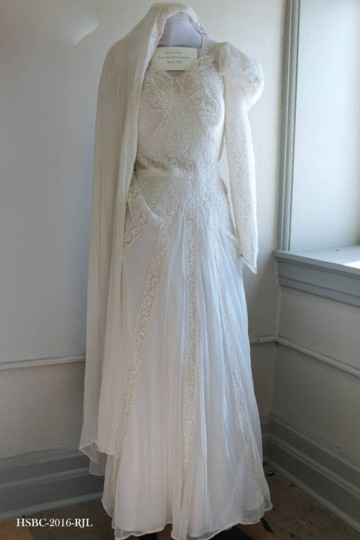 Two-piece Ivory gown made of lace and a sheer material; floor-length with train, with a v-neck cut and long sleeves. Worn by Rosina Schisler at time of her marriage to Charles Elmer Greensfelder on May 3, 1942. Gift of Carol Greensfelder Baublitz. (Photo from the Baltimore Historical Society via Enoch Pratt Library)