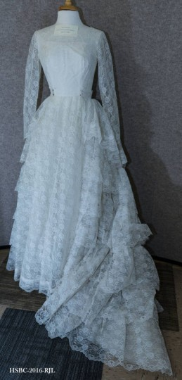 White floor-length wedding dress; long-sleeved with detachable train. Worn by Carol Ann Greensfelder when she wed Benjamin Karl Baublitz, Jr., on April 17, 1966, in Prince of Peace Lutheran Church in Rosedale, MD - the same church that the bride's parents got married in 24 years prior. Gift of Carol Greensfelder Baublitz. (Photo from the Baltimore Historical Society via Enoch Pratt Library)