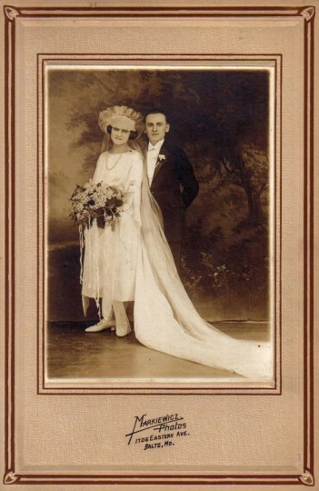 "Black and white wedding portrait of woman in white dress with large bouquet of flowers and train with large headpiece, and man in evening clothes with white boutonniere. Image mounted on beige mat with brown borders and ""Markiewicz Photos"" stamped lower center; sticker on back reads: ""Marie & Anthony Kern (Greensfelder)."" Gift of Carol Greensfelder Baublitz. (Photo from the Baltimore Historical Society via Enoch Pratt Library)"