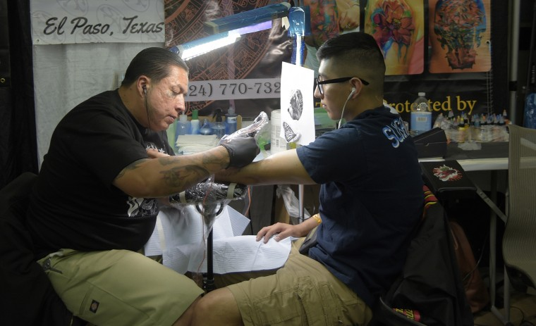 "Chicago Rivera, left, puts a lion and butterfly tattoo on Enriquez Lozano, 19, an active duty soldier from Ft. Meade, MD. Rivera, whose tag is ""Chicago 475"" says, ""Ever since I was a kid, I was really into artwork."" When he was 12, he tattooed his last name on himself. Lozano says, ""I wanted [a tattoo] to represent my parents and myself."" His first tattoo was a bear on his right arm to signify himself. Rivera is tattooing a lion and a butterfly on Lozano's left arm to represent his father and mother respectively. (Algerina Perna/Baltimore Sun)"
