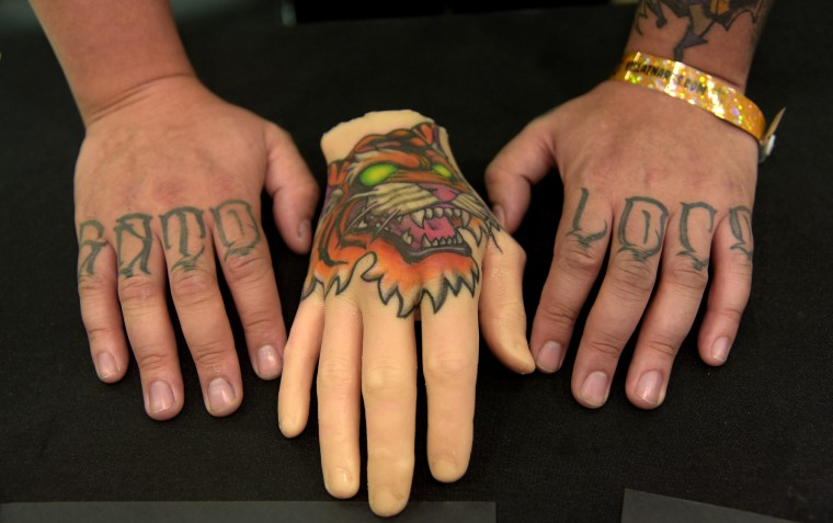 "Tony Maya alias Tig Quest is a tattoo artist from Brooklyn, NY. HIs hands spell ""Gato Loco"" (Crazy Cat).  (Algerina Perna/Baltimore Sun)"