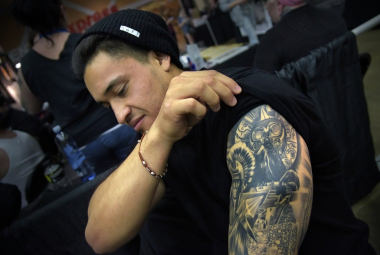 "Honoring his Peruvian ancestry,  Giordano Vittone, 21 from Toms River NJ, was tattooed with an Incan warrior, Machu Picchu and a sun symbol. He says the next tattoo will be the Virgin Mary to honor his Italian ancestry. Vittone says, ""I always like the idea of expressing myself with art- my background, my heritage, so tattooing is the best thing for me. ""The tattoo is by Jesus Kolors Lopez, 21, from Southern California. Vittone and his friend, Paul Samaniego follow Kolors and get their tattoos only from him.  (Algerina Perna/Baltimore Sun)"