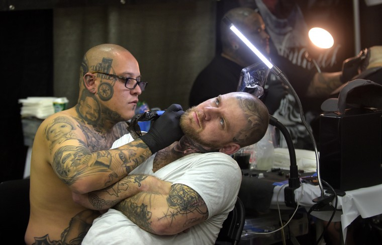 "Carlos Macias, right, tattoos Keith Eby from Harrisburg, PA. Says Macias, 33, who has his own business,  has been tattooing since age 12. He says, ""I didn't know it would take me across the world."" He was invited to Amsterdam for tattooing, and has been to German, Switzerland, Puerto Rico and Brazil for his art.  (Algerina Perna/Baltimore Sun)"