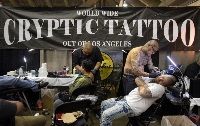 "Jessie Garcia, left, puts a tattoo on Tempest Collins from Laurel, MD while Carlos Macias, right, tattoos Keith Eby from Harrisburg, PA. Says Macias, 33, who has his own business,  has been tattooing since age 12. He says, ""I didn't know it would take me across the world."" He was invited to Amsterdam for tattooing, and has been to German, Switzerland, Puerto Rico and Brazil for his art. (Algerina Perna/Baltimore Sun)"