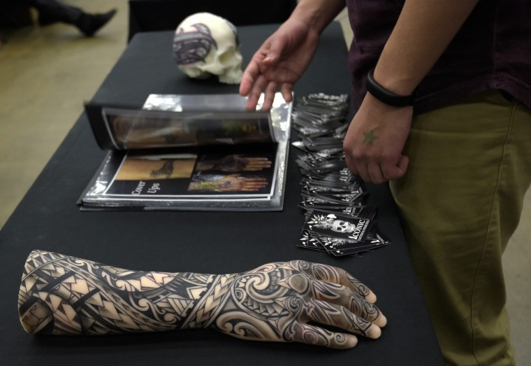 Customers peruse work by tattoo artists displayed at their booths.  (Algerina Perna/Baltimore Sun)