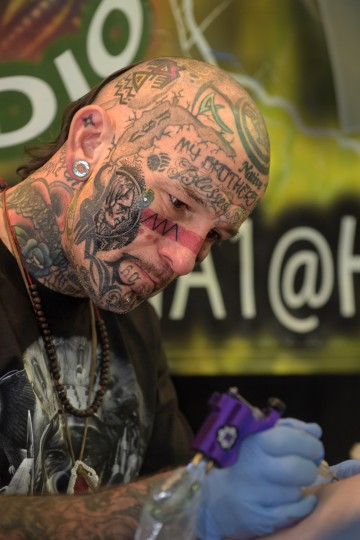 "Joshua ""Two Bears"" Carlton from Panama City, FL who expresses his Native Americn ethnicity in his name and by his tattoos, works on a client. (Algerina Perna/Baltimore Sun)"