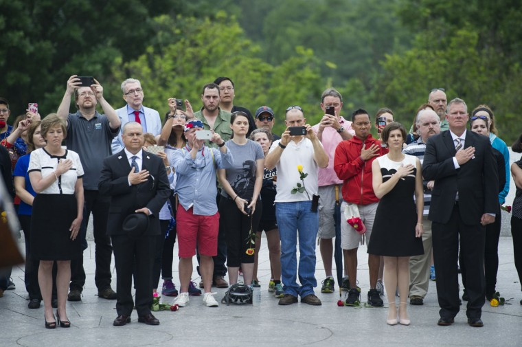 Visitors stand as Taps is played during a wreath laying ceremony at the grave of former President John F. Kennedy, to mark the 100th anniversary of his birth, at Arlington National Cemetery in Arlington, Va., Monday, May 29, 2017. Kennedy was born May 29, 1917. (AP Photo/Cliff Owen)