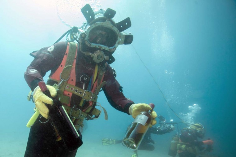 A diver shows bottles from an underwater wine cellar in the Mediterranean sea off Saint-Mandrier, southern France on May 15, 2017. Bandol wine matured underseas before being analyzed after one year. (BORIS HORVAT/AFP/Getty Images)