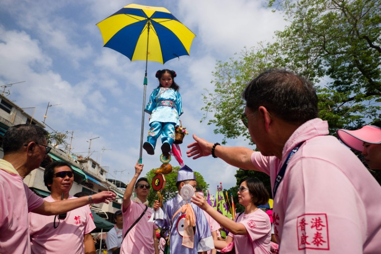 "A young girl dressed as a deity takes part in a parade during the Cheung Chau bun festival on May 3, 2017. Tens of thousands gathered on the Hong Kong outlying island for one of its most colourful festivals, a whirlwind of music and costume culminating in a dramatic climb up a precipitous ""bun tower."" (ANTHONY WALLACE/AFP/Getty Images)"