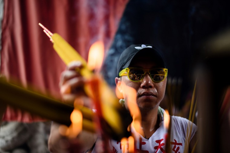 A devotee lights joss sticks in a temple during the annual Cheung Chau Bun Festival. (ANTHONY WALLACE/AFP/Getty Images)