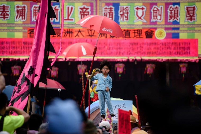 A young girl dressed as chief executive-elect Carrie Lam prepares to take part in a parade during the annual Cheung Chau Bun Festival. (ANTHONY WALLACE/AFP/Getty Images)