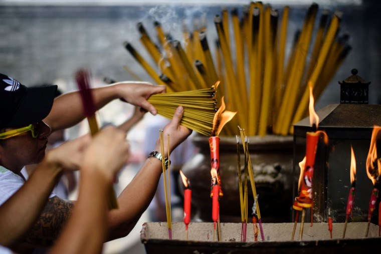 Devotees light joss sticks in a temple during the annual Cheung Chau Bun Festival in Hong Kong on May 3, 2017. (ANTHONY WALLACE/AFP/Getty Images)