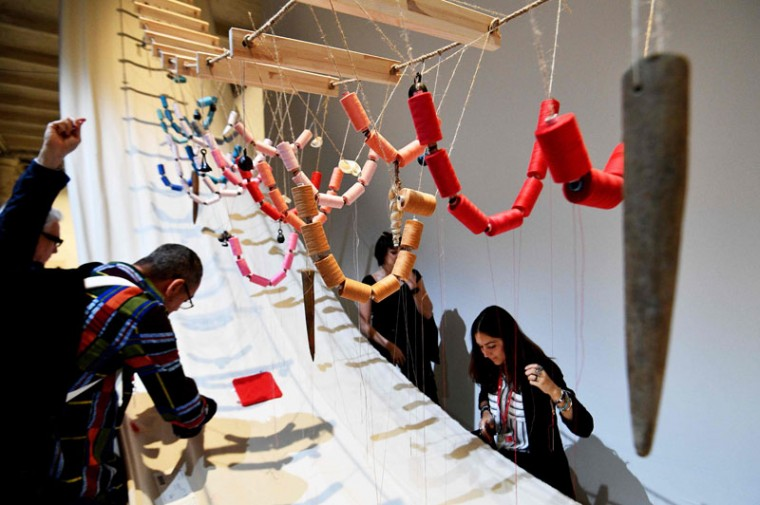 "Visitor interact with the artwork ""A Stitch in Time"" by Czech artist Jana Zelinska during the press preview of the 57th International Art Exhibition Biennale, on May 10, 2017 in Venice. (VINCENZO PINTO/AFP/Getty Images)"