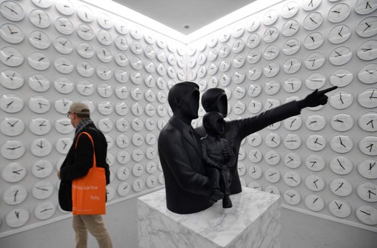 "A visitor admires ""Counterbalance: The Stone and the Mountain,"" made by South Korean artist Lee Wan. (VINCENZO PINTO/AFP/Getty Images)"
