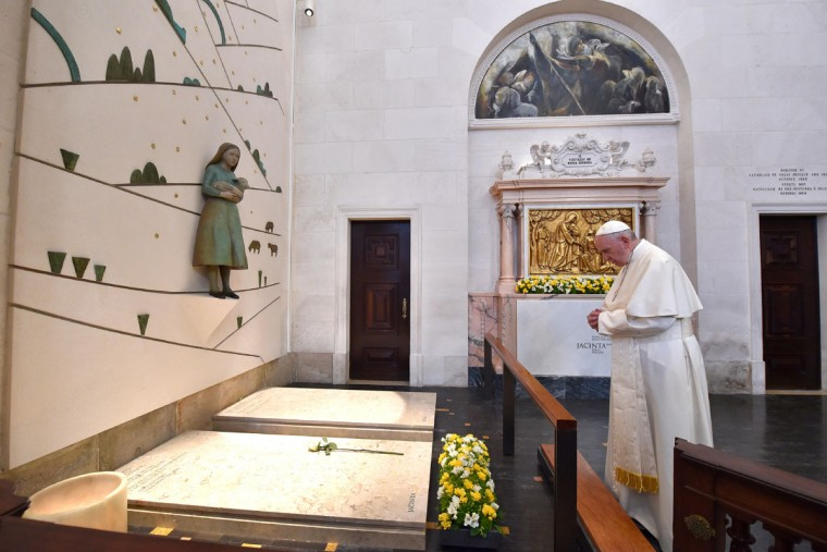 This handout photo taken on May 13, 2017 shows Pope Francis praying in front of the grave of two of the three shepherd children at the Shrine of Our Lady of Fatima in Portugal. The young shepherds, Jacinta and Francisco Marto, saw apparitions of the Virgin Mary 100 years ago in Fatima. (Photo released by the Vatican press office, the Osservatore Romano)