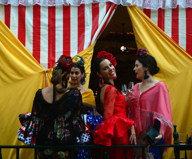 "A woman wearing a traditional Sevillian dress smiles as she drinks ""Fino"" wine with friends during the ""Feria de Abril"" (April Fair) in Sevilla on April 30, 2017. The fair dates back to 1847 when it was originally organized as a livestock fair but has turned into a week of flamenco dancing, music and bullfighting. (Cristina Quicler/AFP/Getty Images)"