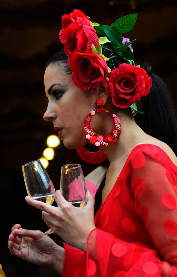 "A woman wearing a traditional Sevillian dress carries two cups of wine during the ""Feria de Abril"" (April Fair) in Sevilla on April 30, 2017. The fair dates back to 1847 when it was originally organized as a livestock fair but has turned into a week of flamenco dancing, music and bullfighting. (Cristina Quicler/AFP/Getty Images)"
