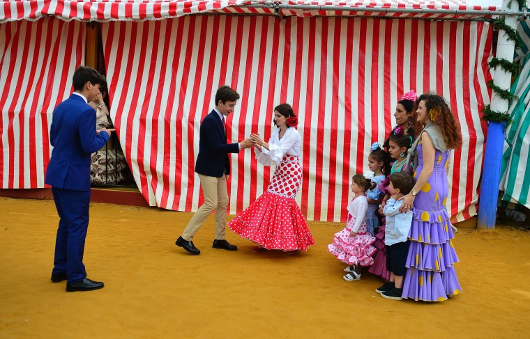 "Family members wearing traditional Sevillian dresses prepare to take a group photo during the ""Feria de Abril"" (April Fair) in Sevilla on April 30, 2017. The fair dates back to 1847 when it was originally organized as a livestock fair but has turned into a week of flamenco dancing, music and bullfighting. (Cristina Quicler/AFP/Getty Images)"