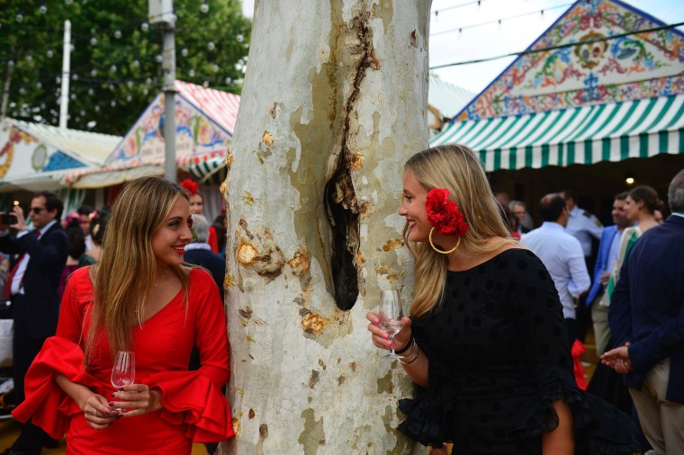 """Two girls wearing traditional Sevillian dresses chat and drink wine during the """"Feria de Abril"""" (April Fair) in Sevilla on April 30, 2017. The fair dates back to 1847 when it was originally organized as a livestock fair but has turned into a week of flamenco dancing, music and bullfighting. (Cristina Quicler/AFP/Getty Images)"""