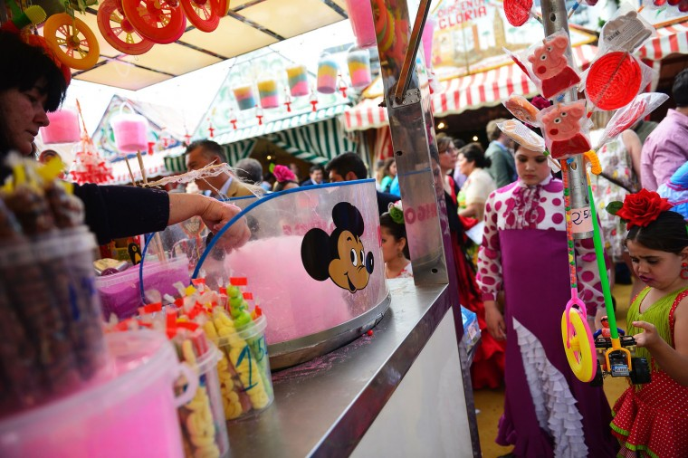 "A woman makes cotton candy during the ""Feria de Abril"" (April Fair) in Sevilla on April 30, 2017. The fair dates back to 1847 when it was originally organized as a livestock fair but has turned into a week of flamenco dancing, music and bullfighting. (Cristina Quicler/AFP/Getty Images)"