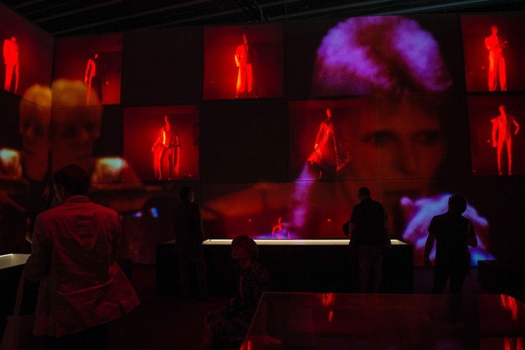 "Visitors watch video projections of British pop icon David Bowie during the exhibition ""David Bowie is"" at the Museum of the Design of Barcelona, on May 24, 2017. (Josep Lago/AFP/Getty Images)"