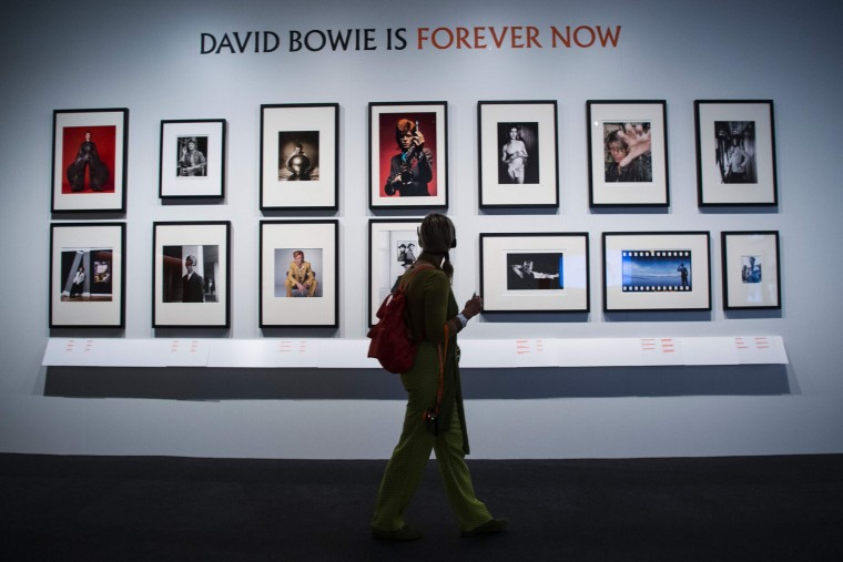 "A woman looks at pictures of US artist David Bowie during the exhibition ""David Bowie is"" at the Museum of the Design of Barcelona, on May 24, 2017. (Josep Lago/AFP/Getty Images)"