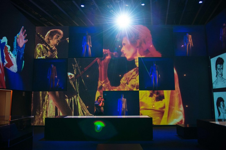 "A man takes pictures of video projections of British pop icon David Bowie during the exhibition ""David Bowie is"" at the Museum of the Design of Barcelona, on May 24, 2017. (Josep Lago/AFP/Getty Images)"