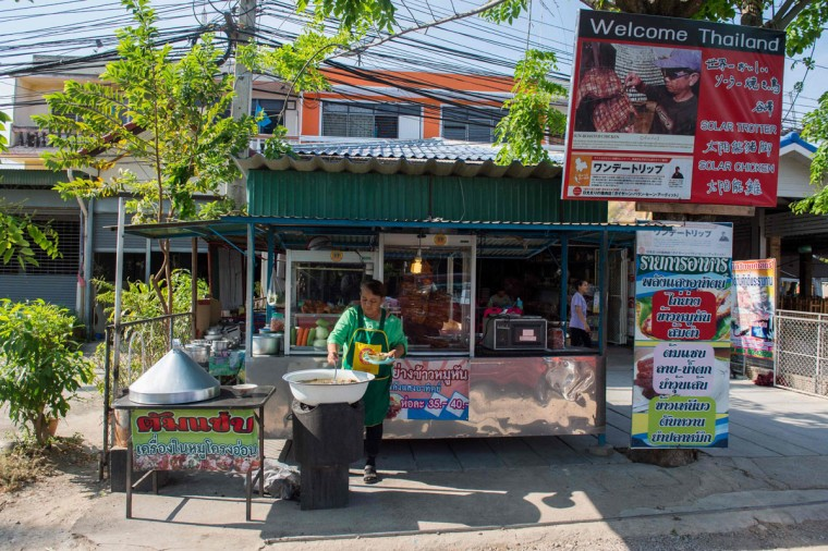 This picture taken on May 4, 2017 shows Mali Pansari, the wife of vendor food vendor Sila Sutharat, tending to their eatery where they sell chicken and pork cooked by solar rays in Petchaburi province, south of Bangkok. Not many chefs don a welding mask before they enter the kitchen, but Sila Sutharat prefers to cook his chicken sunny side up. Two hours south of Bangkok this 60-year-old vendor has found an ingenious way to offer his customers something a little different by harnessing the power of the sun. Using a large wall of nearly 1,000 moveable mirrors -- a device he designed and built himself -- he focuses the sun's rays onto a row of marinated chickens, sizzling away under the intense heat. (ROBERTO SCHMIDT/AFP/Getty Images)