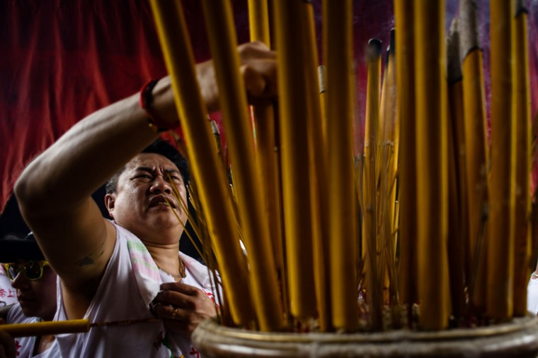 A devotee places his joss stick in an urn at a temple during the annual Cheung Chau Bun Festival in Hong Kong on May 3, 2017.(ANTHONY WALLACE/AFP/Getty Images)